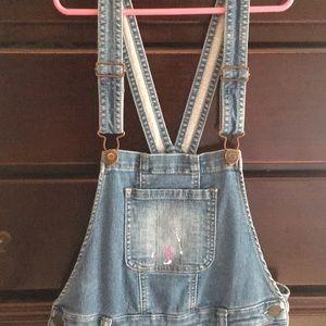 Cute girls paint splattered overalls